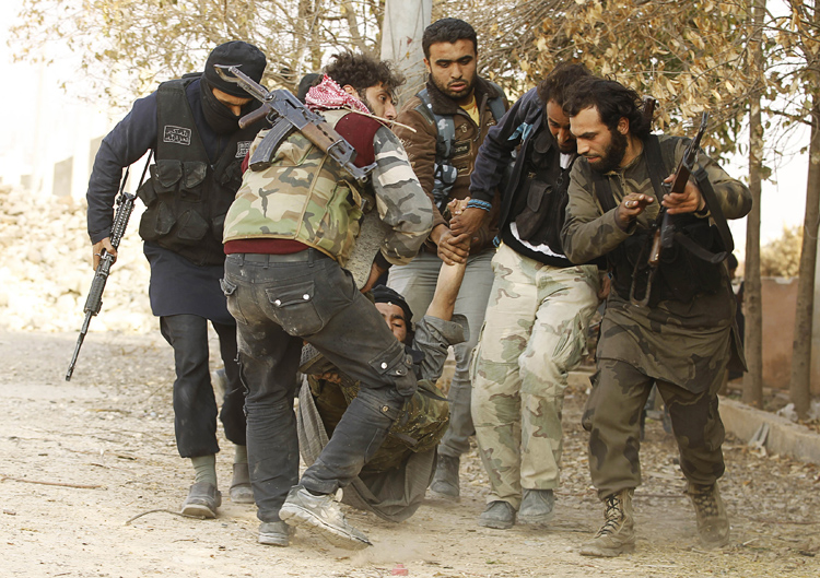Free Syrian Army fighters carry a fellow fighter who was wounded during clashes with forces loyal to Syria's President Bashar al-Assad near Base 80 near Aleppo International airport